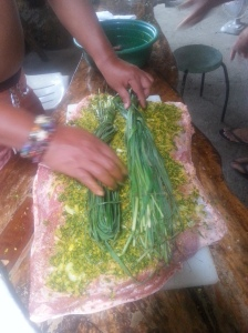 Rubbing the babi guling with spices.